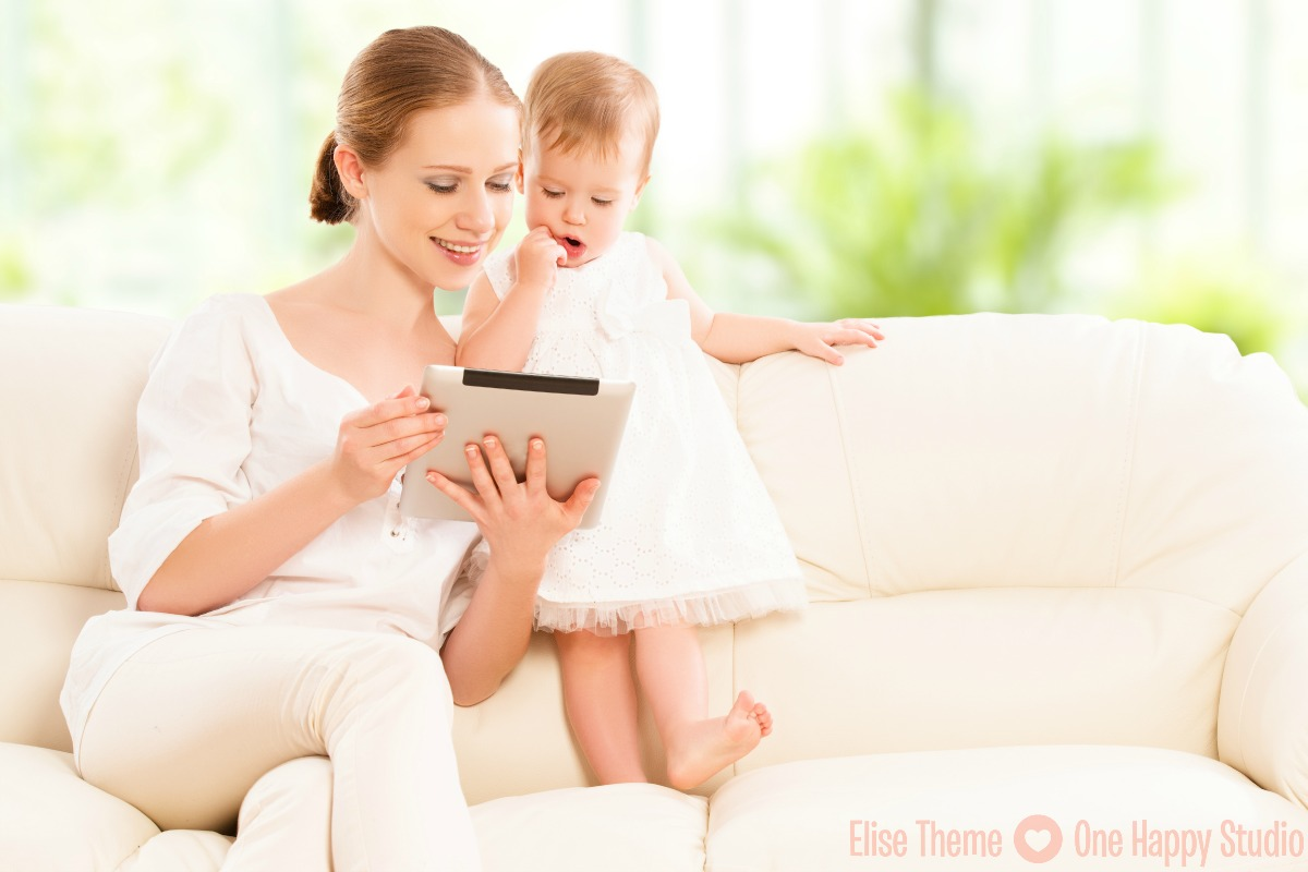 mother and baby child are looking to play and read tablet computer on the couch at home