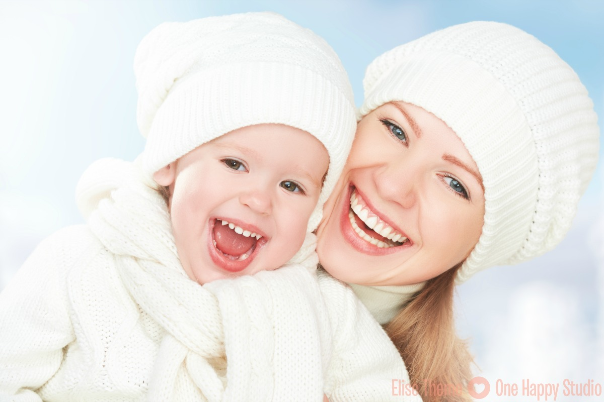 Mother and baby daughter in the white hats laughing